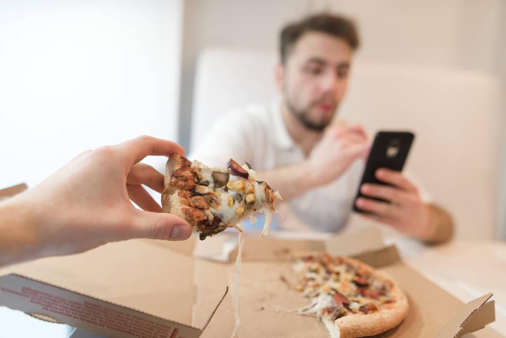 ест с телефоном в руке